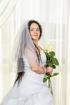 Uma noiva judia está em uma sinagoga antes de uma cerimônia huppa durante uma pandemia, usando uma máscara médica e um buquê de flores