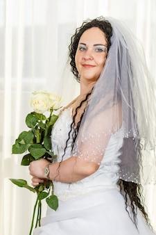 Uma noiva judia está no corredor antes da cerimônia chuppa com um buquê de rosas brancas nas mãos, uma foto na cintura