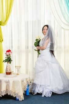 Uma noiva judia está no corredor antes da cerimônia chuppa em uma mesa com flores e um buquê de rosas brancas nas mãos