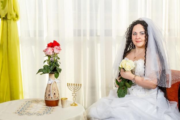 Uma noiva judia feliz com um buquê de rosas brancas está sentada na sinagoga antes da cerimônia huppa em uma mesa com flores e uma menorá. foto horizontal.