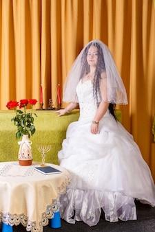 Uma noiva judia feliz em um vestido branco exuberante, seu rosto coberto por um véu, está na sala antes da cerimônia chupá. foto vertical