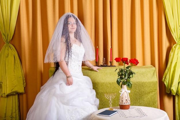 Uma noiva judia feliz em um vestido branco fofo, seu rosto coberto com um véu, está na sala à mesa antes da cerimônia chupa. foto horizontal