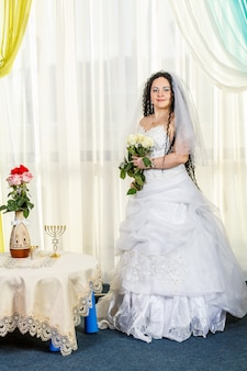 Uma noiva judia feliz está no corredor antes da cerimônia chuppa em uma mesa com flores e um buquê de rosas brancas nas mãos. foto vertical