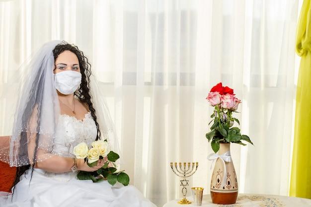 Uma noiva judia se senta em uma sinagoga com um stlik antes de uma cerimônia de chuppa durante uma pandemia, usando uma máscara médica e um buquê de flores
