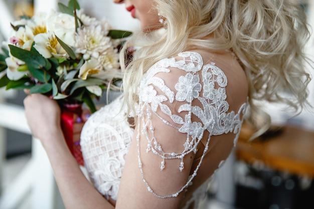 Uma noiva loira com cabelo comprido segura um buquê de casamento na moldura do ombro com os detalhes do vestido de noiva
