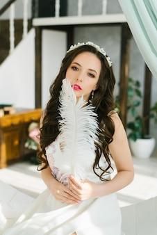 Uma noiva morena linda em um vestido de noiva branco com uma tiara no cabelo tem uma pena de avestruz nas mãos.