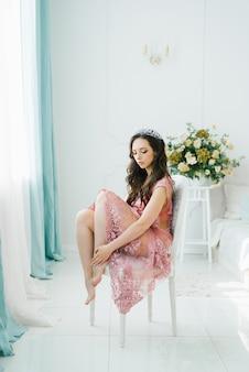 Uma noiva morena linda em um vestido rosa boudoir senta-se em uma cadeira com as pernas dobradas sob ela em um quarto clássico e claro.