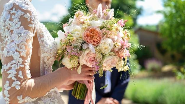 Uma noiva segurando um buquê exuberante, vista de perto, cerimônia de casamento