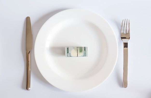 Uma nota de um dólar em um prato branco entre um garfo e uma faca na superfície branca