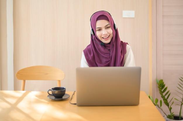 Uma operadora muçulmana usando fone de ouvido usando computador, atendendo chamadas de clientes no escritório, conceito de atendimento ao cliente