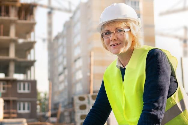 Uma operária da construção civil usando um colete e um capacete no fundo de um novo edifício