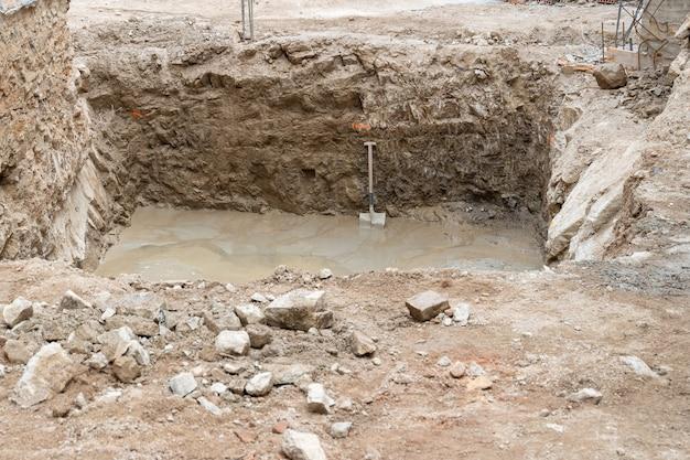 Uma pá de alvenaria repousa sobre uma das paredes do buraco para a fundação de uma nova casa