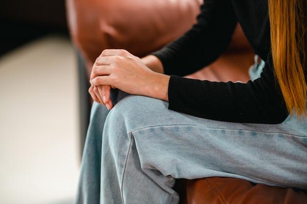 Uma paciente segura a mão dela enquanto procura a consulta com um psicólogo.