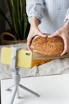 Uma padeira conta uma receita de pão on-line em um blog de culinária com cursos de culinária em vídeo sobre como assar pão