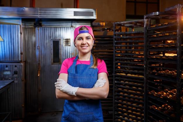 Uma padeira profissional está perto de uma prateleira com bandejas de biscoitos frescos. doces em padaria