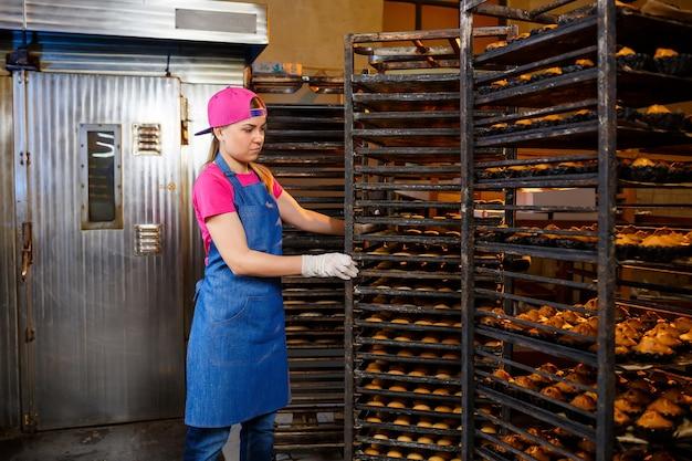 Uma padeira profissional está perto de uma prateleira com bandejas de biscoitos frescos. pastéis doces em padaria