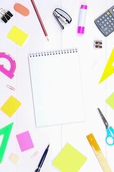 Uma página de caderno em branco cercada por artigos de papelaria na mesa de madeira branca. copie o espaço.