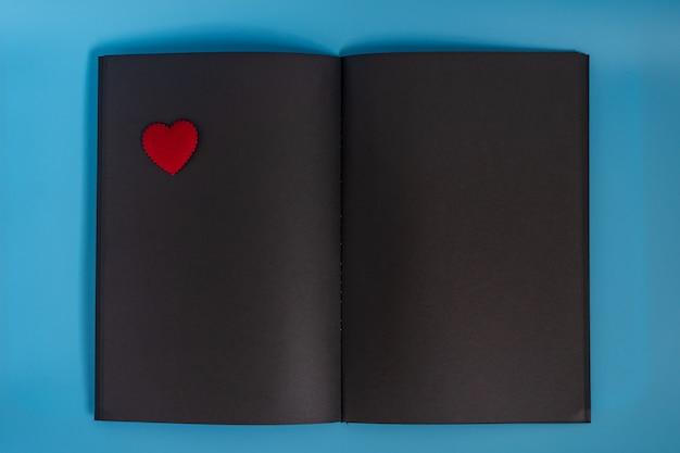 Uma página em branco do caderno de papel preto deitado no fundo azul, caderno aberto