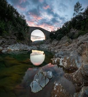 Uma paisagem surpreendente que funde o reflexo dramático do pôr-do-sol no céu de um rio entre rochas e uma ponte medieval na espanha