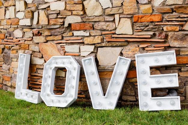 Uma palavra de amor perto da parede de pedra. área de foto na decoração de casamento no parque