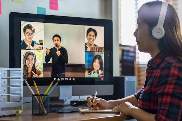 Uma palestra de escrita de mão de mulher asiática do close up durante o aprendizado on-line por meio de videoconferência com o professor