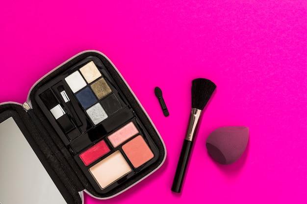Uma paleta de sombra aberta com escova e liquidificador no fundo rosa