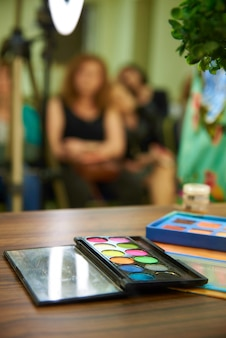 Uma paleta de sombras brilhantes para maquiagem no fundo desfocado. Foto Premium