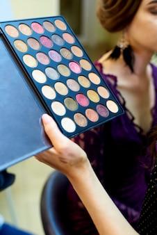 Uma paleta de sombras para maquiagem nas mãos de um artista de make-up.