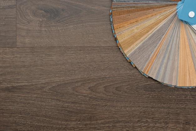Uma paleta de texturas e decoração para o piso de madeira do laminado e vinil em uma mesa de madeira escura. design de interiores. planejando e construindo uma casa.