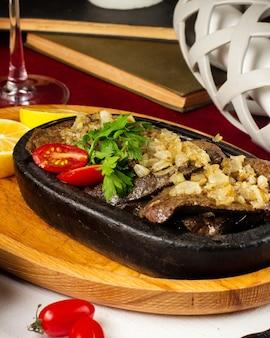 Uma panela de ferro fundido com carne frita e cebola salteada