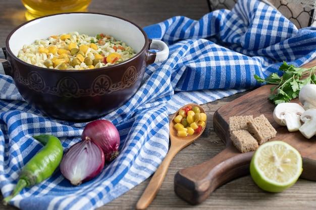 Uma panela de macarrão com legumes e uma colher na toalha de mesa