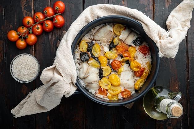 Uma panela de peixe fabuloso, com arroz basmati e tomate cereja, na velha mesa de madeira, vista de cima