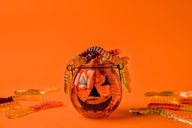 Uma panela em forma de abóbora está cheia de minhocas de geléia em um conceito de fundo laranja de hallowee