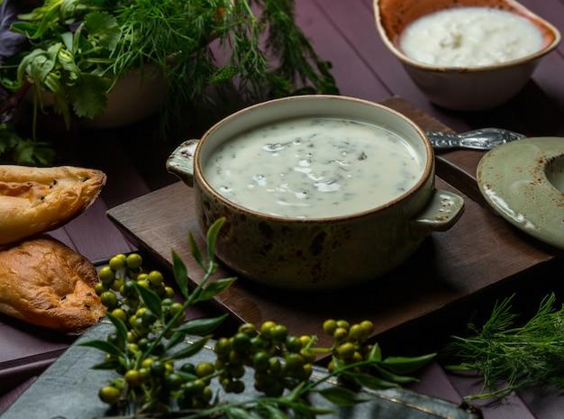 Uma panela verde de sopa de iogurte com ervas