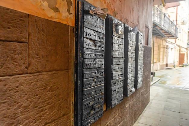 Uma parede com fileiras de caixas de correio em um edifício residencial de vários andares.