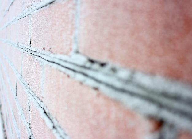 Uma parede de tijolos congelados na neve branca
