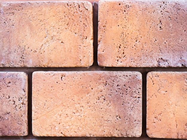 Uma parede de uma fachada artificial de pedra bege e vermelha com superfícies fraturadas e ásperas, dispostas como um tijolo