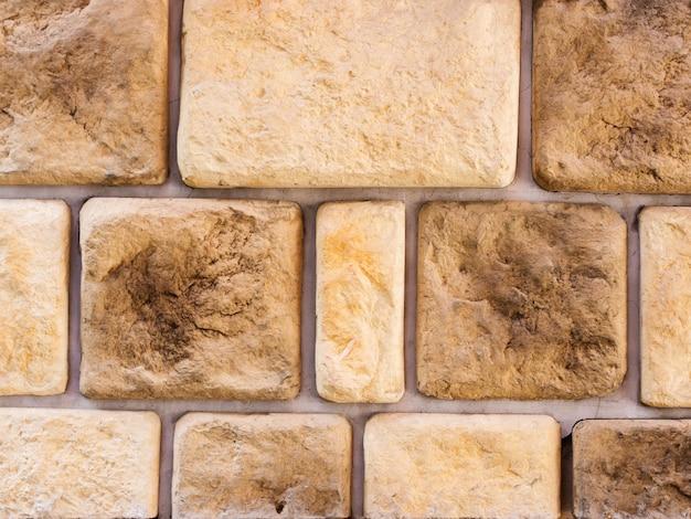Uma parede de uma fachada artificial de pedra cinza com superfícies fraturadas