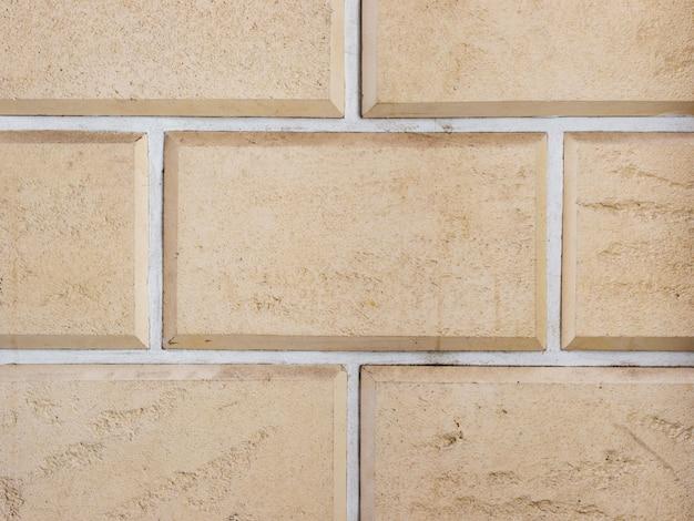 Uma parede de uma fachada de pedra bege artificial com superfícies fraturadas e ásperas, dispostas como um tijolo