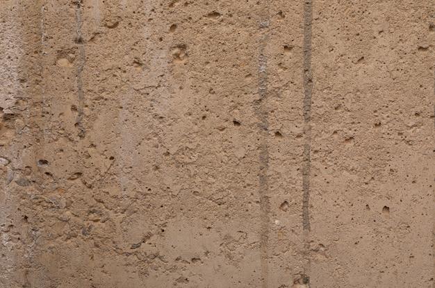 Uma parede emplastrada desigual bege velha