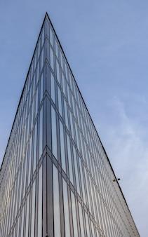 Uma parte aguda de um edifício moderno voltado para o céu azul.