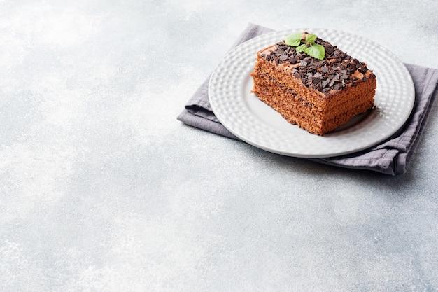 Uma parte de bolo da trufa com chocolate em um fundo concreto cinzento. espaço da cópia