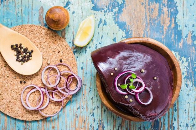 Uma parte de fígado cru da carne em uma bacia, em uma cebola, em um limão e em umas especiarias para cozinhar em uma tabela de madeira. vista do topo