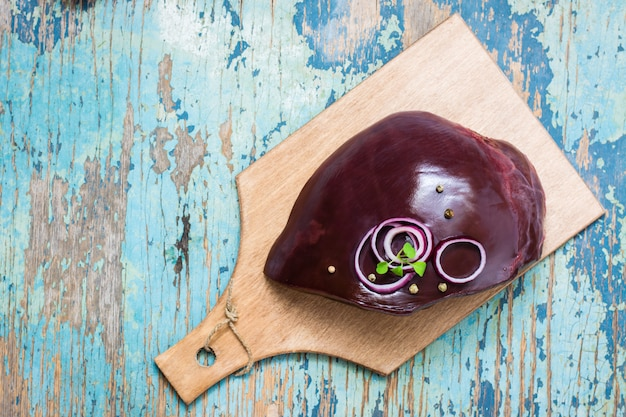 Uma parte de fígado cru da carne em uma placa de corte, cebola e especiarias para cozinhar em uma tabela de madeira. vista do topo