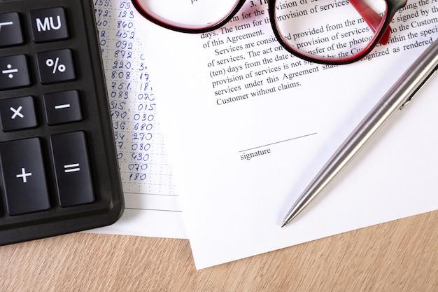 Uma parte do contrato ou documento do acordo, espaço de assinatura com caneta de prata, óculos e calculadora.