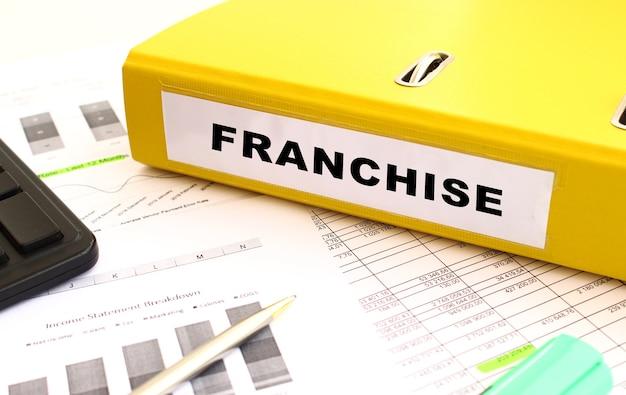 Uma pasta amarela com documentos etiquetados como franquia está na mesa do escritório com gráficos financeiros