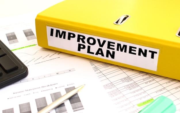 Uma pasta amarela com documentos etiquetados como plano de melhoria está na mesa do escritório com gráficos financeiros