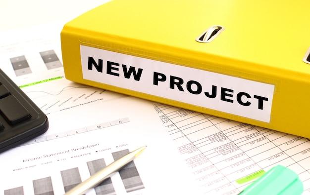 Uma pasta amarela com documentos rotulados como novo projeto está na mesa do escritório com gráficos financeiros