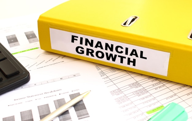 Uma pasta amarela com documentos rotulados crescimento financeiro está na mesa do escritório com gráficos financeiros. conceito financeiro.