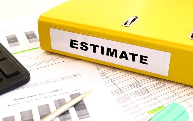 Uma pasta amarela com documentos rotulados estimate repousa sobre a mesa do escritório com gráficos financeiros.
